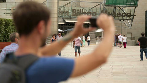 Tourist taking video with smartphone in front of museum in Bilbao, travel Footage