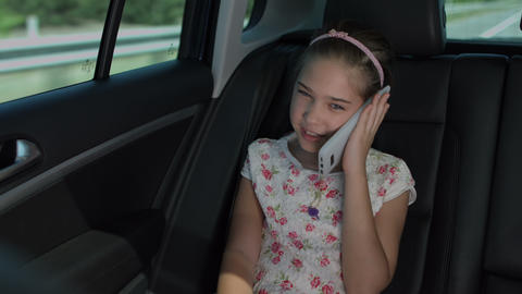 Adorable girl talking on cellphone in luxury car Footage