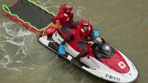 Rescuers sitting on water motorcycle with water stretcher behind, first aid Footage
