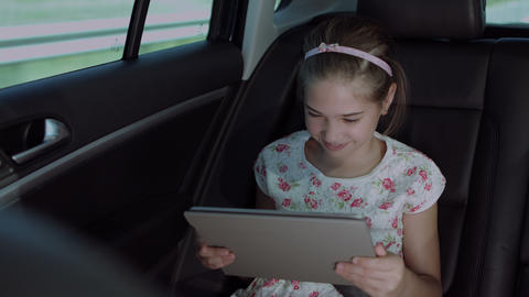 Happy girl watching cartoons on tablet in the car Footage