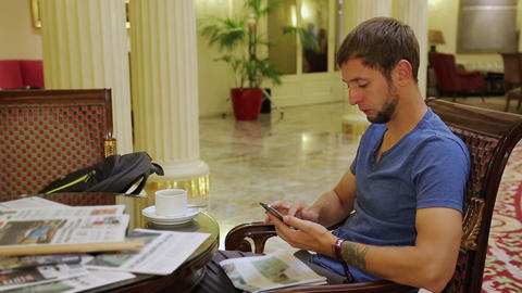 Man sitting at table in hotel lobby and checking morning news, a coffee on table Live Action