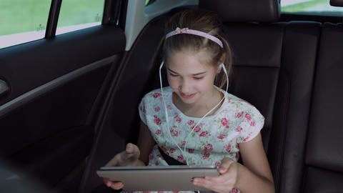 Child playing online game with tablet pc in car Footage