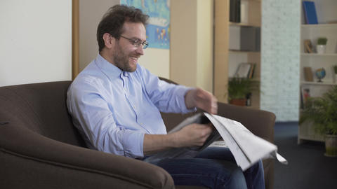 Joyful man reading horoscope in newspaper and enjoying life, weekend at home Footage