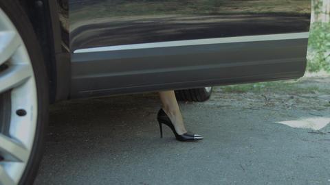 Slim female legs in high heels getting out of car Footage