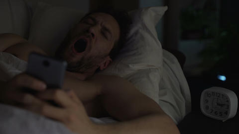 Young adult man can't sleep, yawning and browsing the net on cellphone, insomnia Live Action