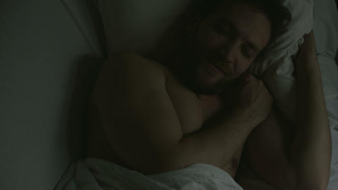 Sweet sleep of handsome adult man lying in bed, smiling during naptime, relax Footage