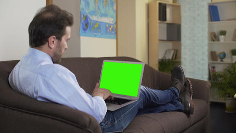 Man sitting on sofa and watching favorite movie on laptop with green screen Footage