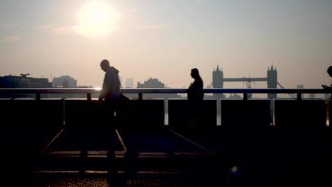 London - Commuters on London Bridge at sunrise. Zoom out - People Tower Bridge Footage