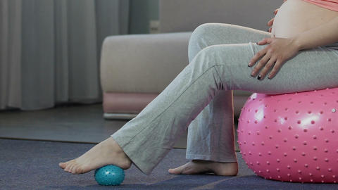 Mother-to-be sitting on fitness ball, massaging feet with rubber ball, body care Live Action