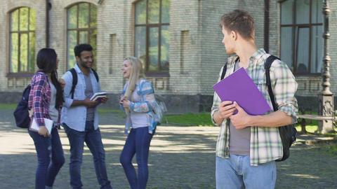 Lonely male student looking at happy laughing classmates standing near college Footage