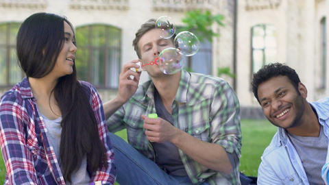 Young man lying on grass with best friends and blowing bubbles, carelessness Footage