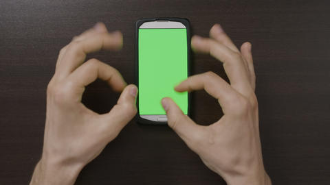 Top view of millennial man hands gesturing in front of green screen smartphone Footage