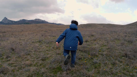 A boy on field with yellow flowers run to horizon with rocks. Slow motion video Footage