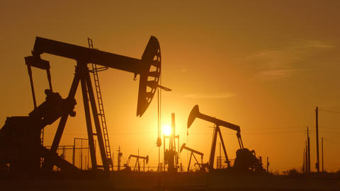 The silhouette of oil pumps in a large oil field at sunrise Footage