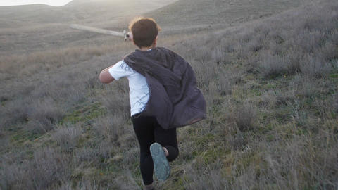 A boy with a sword runs to the horizon at sunset. Slow Motion video Footage
