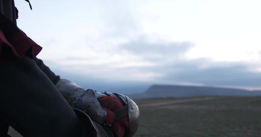 Camera smooth glide from garda to face of the knight that looks to horizon Live Action