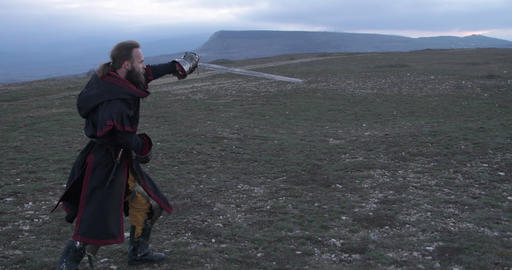 Knight fencing his sword against the backdrop of the mountains at sunset Live Action