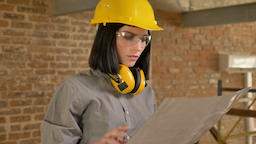 Young charming architect woman holding paper and looking forward, concentrated Footage