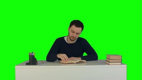 Tired man reading a book in a library on a Green Screen Footage
