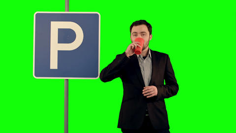 Man with cup of tea near parking sign on a Green Screen Footage