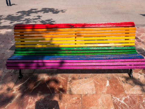 bench in a park painted in the colors of the rainbow flag in Valencia, Spain Photo