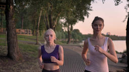 Two young beautiful female runners with ponytails jogging in park near river Footage