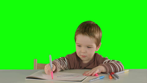 A son drawing at the table at home on a Green Screen Footage