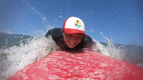 camera on surf board of a young surfer Indonesian man paddling aggressively and Footage
