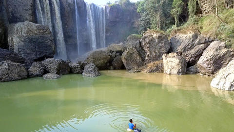 person fishes from lifebuoy opposite foamy waterfall Footage