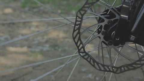 Spinning bicycle wheel against a brick wall in the background Footage