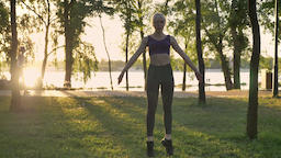 Young pretty woman doing star exercise in park, weight loss, fitness model Footage