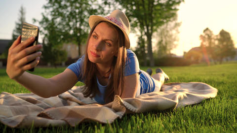 Girl making a selfie lying down on a blanket in the park at sunset Footage