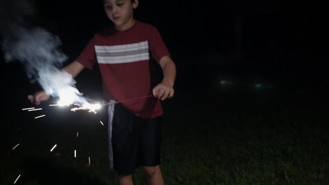 8 - 10 year old boy holding fireworks and sparklers and looking mesmerized as Footage