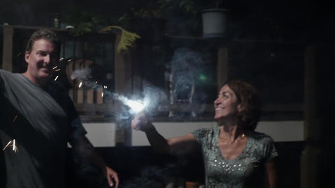 Happy man and woman smiling and waiving sparklers and fireworks at a holiday Footage