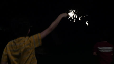 Happy young boy jumping up and down with a sparkler in his hand at night in slow Footage