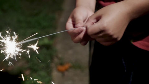 Close up of a young boy holding a sparkler in his hand at night Footage