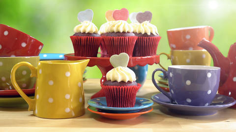 Tea party with cupcakes and rainbow colored polka dot cups and saucers, static Live Action