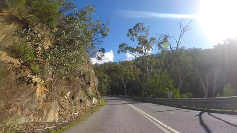Driving along mountain road on a sunny afternoon, with lens flare, vehicle POV. Footage