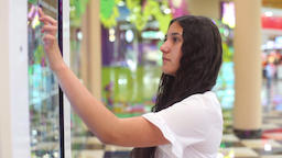 Young Girl uses an interactive panel while making an online purchase at the mall ビデオ