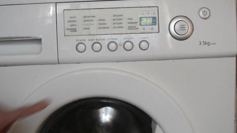 The man presses the start button of washing Footage