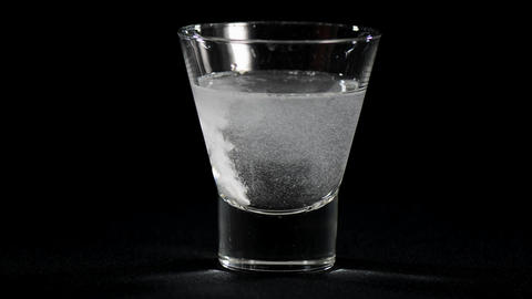 Dissolving one pain killer preparation tablet in glass of water against a black Footage