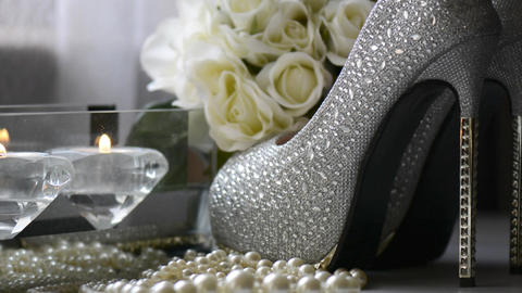 High heel stiletto shoes, bouquet of white roses, jewelry and lit candles on Footage