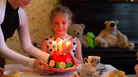 girl blows on a pie with candles Footage