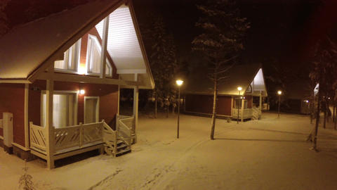 Flying over small wooden house in winter evening Footage