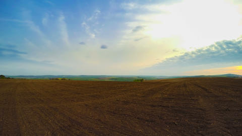 Ploughed Land and Clouds. Panorama. Time Lapse UHD Footage