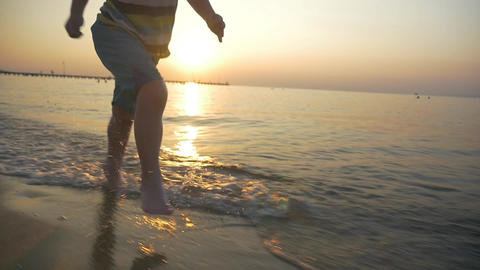 Barefoot kid running in sea water at sunset Footage