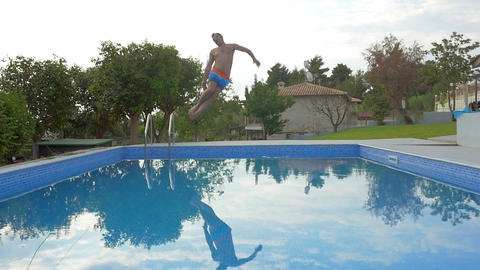 Man jumping into the outdoor pool Footage