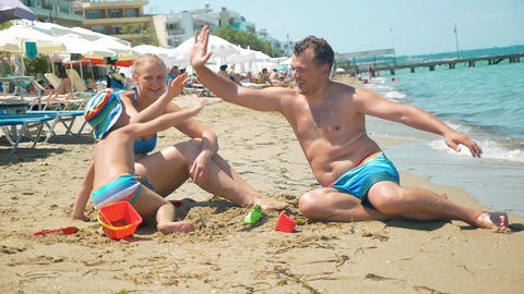 Family of three giving hi-fives on the beach Footage