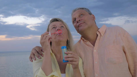 Happy senior couple blowing bubbles on the beach Footage