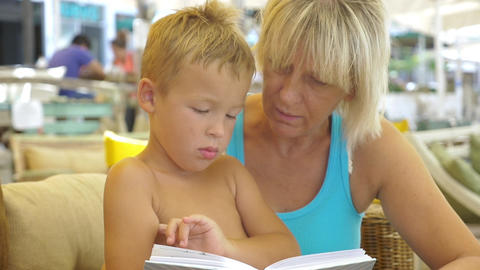 Grandmother reading a book to grandson Footage